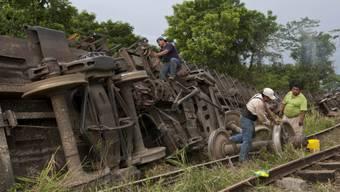 Männer machen sich am entgleisten Zug in Mexiko zu schaffen