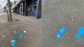 Blaue Füsse am Boden weisen den Weg von der NAB-Filiale zur AKB-Niederlassung
