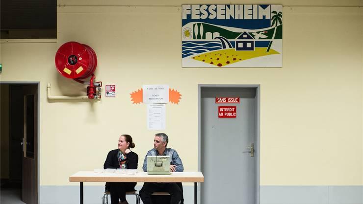 Kasse in der Mehrzweckhalle von Fessenheim, wo Lotto gespielt wird. Das AKW schmuggelt sich stilisiert auf dem Plakat zum Dorf dann doch ins Bild.