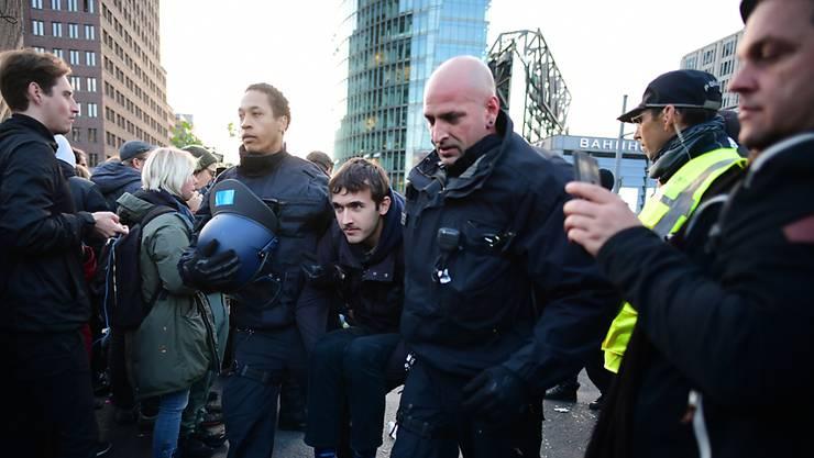 """Die Polizei führt """"Rebels"""" von Extinction Rebellion vom Potsdamer Platz in Berlin ab."""