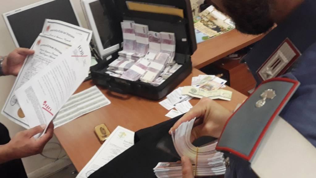 Polizeibeamte halten Geld und Papiere in den Händen. Die italienische Polizei hat fünf Menschen festgenommen. Sie hatten sich als Vermittler des Vatikans ausgegeben und damit ihre Opfer um hohe Geldsummen betrogen, teilten die Carabinieri in Rom am 08.07.2021 mit.