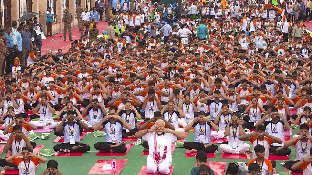 Der indische Premierminister Narendra Modi (Mitte, kniend) macht zusammen mit tausenden andern in Lakhnau Yoga-Übungen zum Weltyogatag.