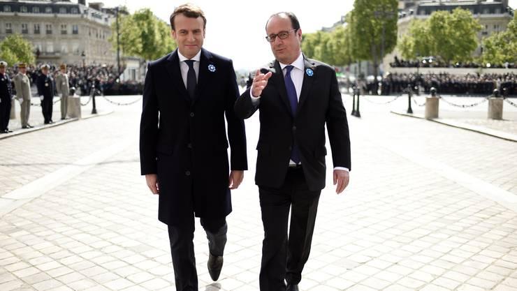 Der künftige französische Präsident Emmanuel Macron (l.) und Amtsinhaber François Hollande auf dem Weg zum Grab des unbekannten Soldaten.