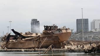 Menschen stehen nach der Explosion im Hafen von Beirut an der Unglücksstelle. Foto: Thibault Camus/AP Pool/dpa