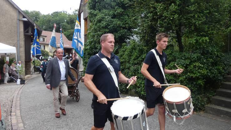 Unter Trommelwirbeln von Tambouren zog der kleine Festumzug durchs Gelände des Räbfeschts in Oberflachs. Regierungsrat Markus Dieth (links) half dabei das Weinfass auf einem Wagen zu ziehen.