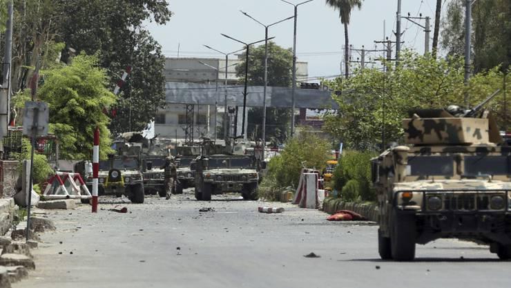 Afghanische Sicherheitskräfte versammeln sich nach einem Angriff in der Stadt Dschalalabad vor einem Gefängnis. Foto: Rahmat Gul/AP/dpa