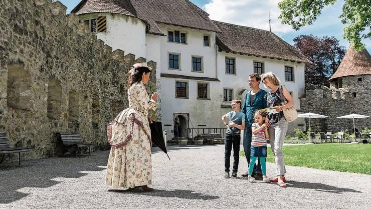 Eine coronakonforme Interaktion: Die historische Figur Cäcilia von Im Hoff erzählt einer Familie aus dem Wallis über die Geschichte des Schlosses.