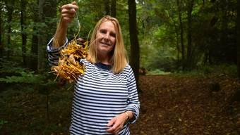 Spielgruppenleiterin Barbara Storr zeigt eine Dekoration aus Blättern und Kastanien, die sie mit den Kindern bastelt.
