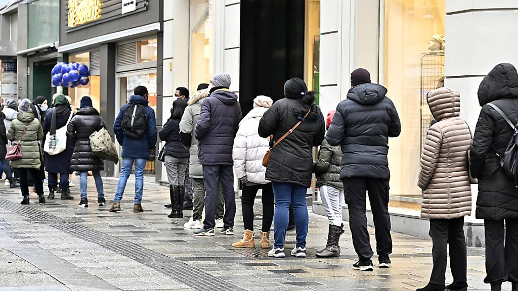 Kunden stehen vor einem Geschäft in Wien in einer Schlange. Nach fast drei Wochen Corona-Lockdown dürfen in Österreich Geschäfte, Einkaufszentren, Friseure und andere Dienstleister unter strengen Auflagen wieder öffnen. Foto: Hans Punz/APA/dpa
