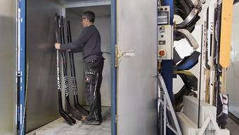 """In Handarbeit wird im Jura der einzige Schweizer Eishockeystock hergestellt. Hier stellt ein Mitarbeiter der Firma Busch einige Stücke in einen Ofen, in dem diese während acht Stunden bei 70 bis 80 Grad """"gebacken"""" werden."""