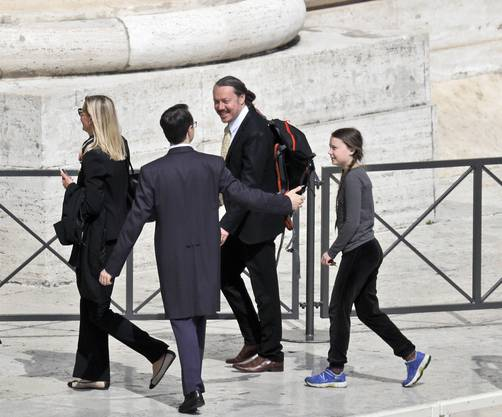 Swedish teenage environmental activist Greta Thunberg, right, and her father Svante Thunberg, center, are escorted as they leave after attending Pope Francis weekly general audience in St. Peter's Square, at the Vatican, Wednesday, April 17, 2019. (AP Photo/Gregorio Borgia)