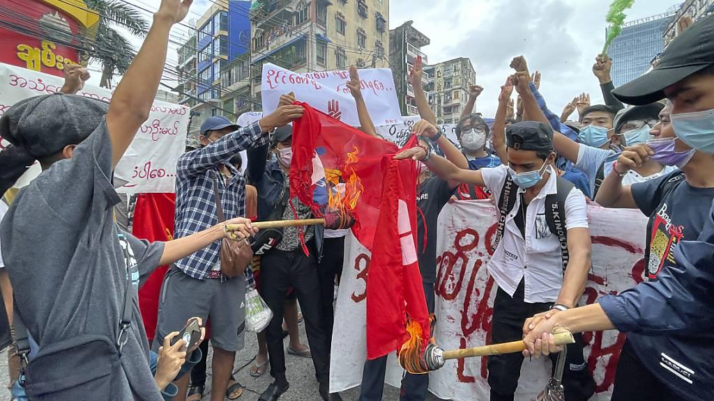 ARCHIV - Demonstranten verbrennen eine Fahne der myanmarischen Armee während eines Protests. Foto: Uncredited/AP/dpa