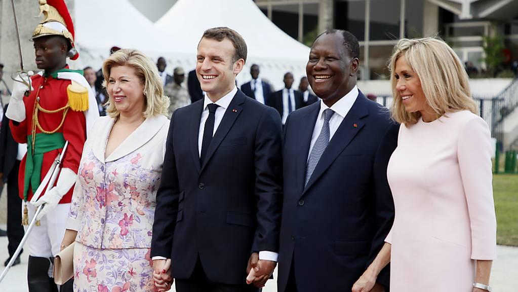 Der französische Präsident Emmanuel Macron (Mitte) mit seiner Gattin Brigitte (rechts) und seinem Amtskollegen aus der Elfenbeinküste, Alassane Ouattara, sowie dessen Gattin Dominique Folloroux-Ouattara in Abidjan.
