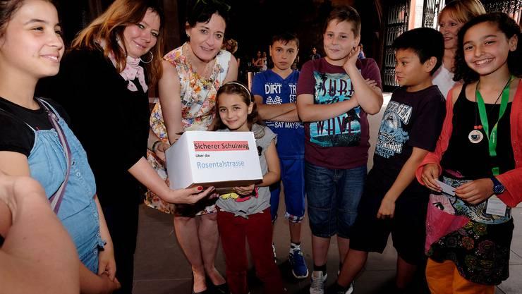 Grossrätin Brigitta Gerber und Barbara Schüpbach-Guggenbühl, Leiterin Staatskanzlei BS, nehmen von denSchülern, stellvertretend die 9-jährige Akasya Kül, die Petition entgegen.