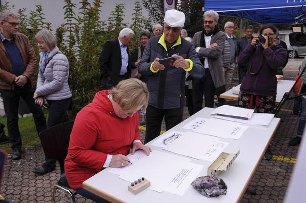 Die Vertreter unterschreiben Dokumente welche in den versiegelten Zeitkapseln in der Kugel aufbewahrt werden.