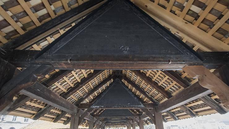 Die heute vor 25 Jahren abgebrannte Luzerner Kapellbrücke war rasch wieder aufgebaut. Wie mit den verbrannten Bildern im Dachgiebel umgegangen werden soll, wird aber auch heute noch diskutiert.