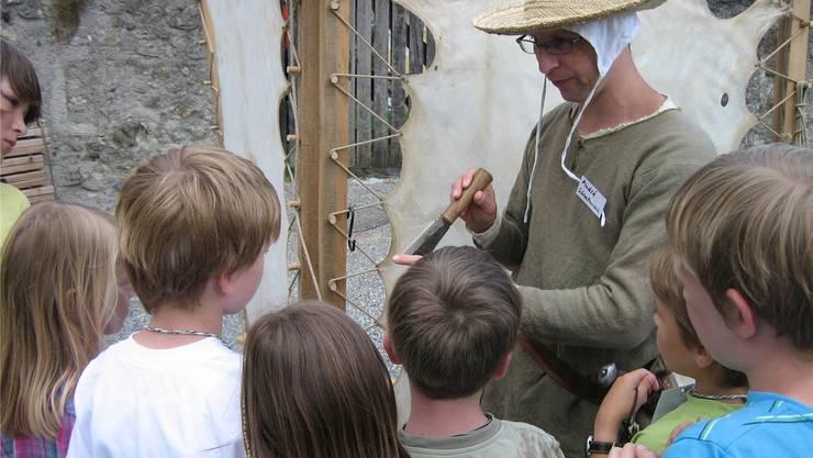 André Schnellmann zeigt Kindern, wie man Pergament herstellt.bär