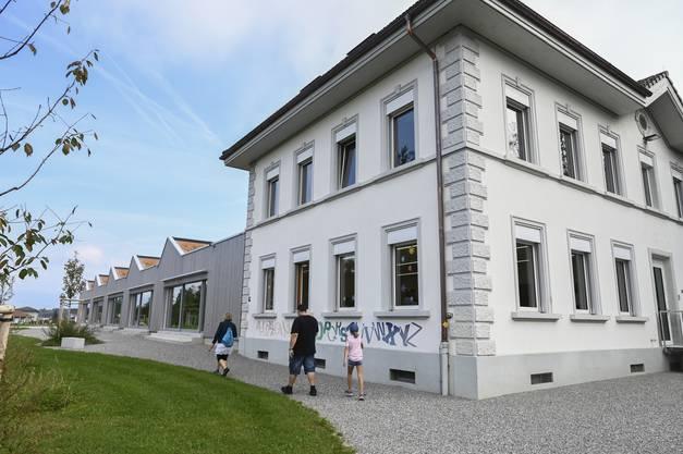 """Aussenaufnahme des renovierten alten Schulhauses mit dem Neubau """"Toblerone""""."""