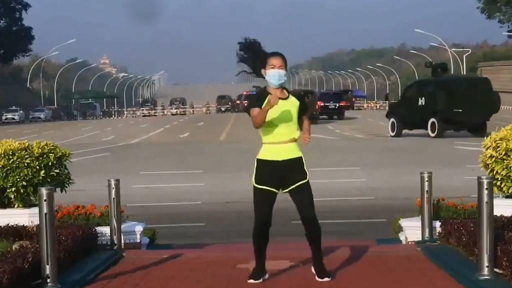 Sie tanzt fröhlich ihre Aerobic-Choreo, im Hintergrund fahren Militärkonvois auf