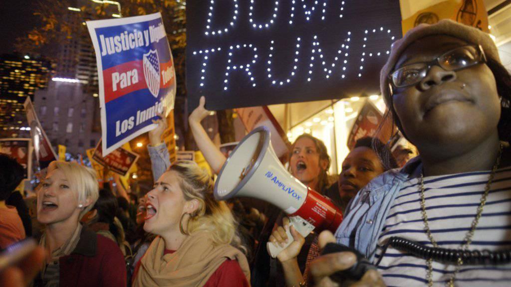 """Protest in New York gegen Trump und dessen Auftritt in der Sendung """"Saturday Night Live"""". Auf dem Transparent steht auf deutsch übersetzt: """"in den Müll mit Trump"""""""