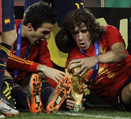 Carles Puyol und Cesc Fabregas spielen 2010 mit dem WM-Pokal in Johannisburg. Eben ist Spanien gegen Holland Weltmeister geworden.
