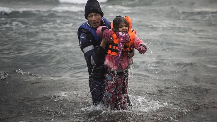 Ein Mann trägt ein Mädchen von einem Flüchtlingsboot an die Küste von Lesbos. Der diesjährige Nansen-Preis ehrt die vielen freiwilligen Helfer an Griechenlands Küsten während der Flüchtlings-Krise. (Archiv)