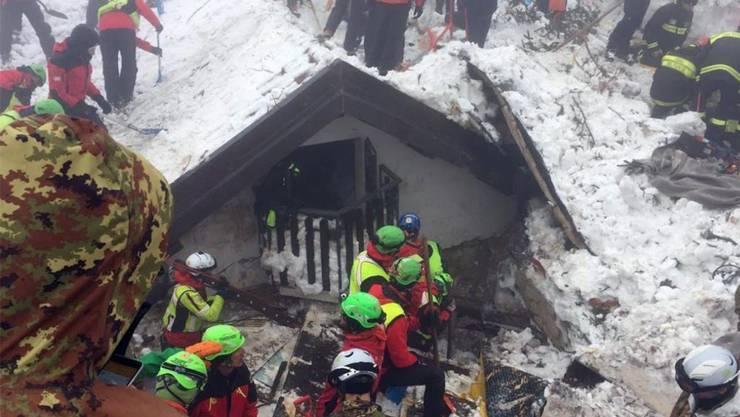Helferinnen und Helfer suchen in den Trümmern des Hotels nach Überlebenden.