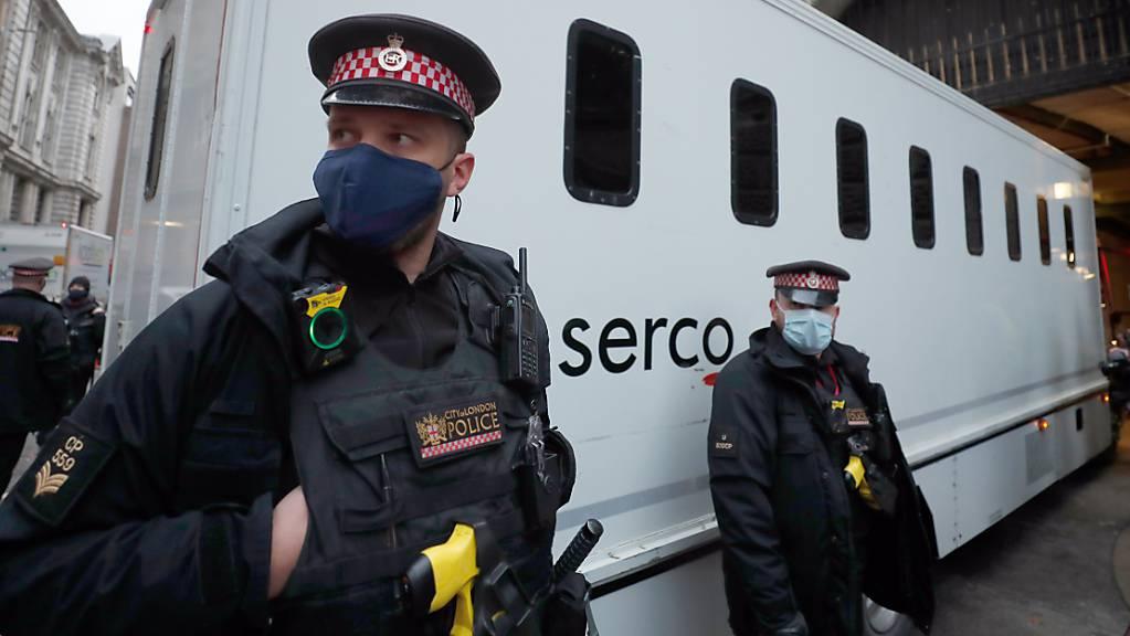 Polizisten sichern einen Gefangenentransporter, der vor der Urteilsverkündung im Auslieferungsprozess gegen Julian Assange am Strafgerichtshof Old Bailey eintrifft. Das Gericht hat den US-Auslieferungsantrag abgelehnt. Foto: Frank Augstein/AP/dpa
