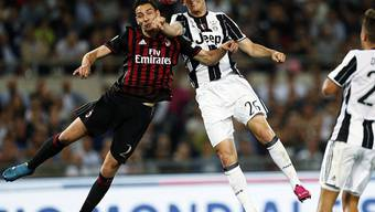 Milans Mattia De Sciglio (links) hält gegen Juves Stephan Lichtsteiner dagegen