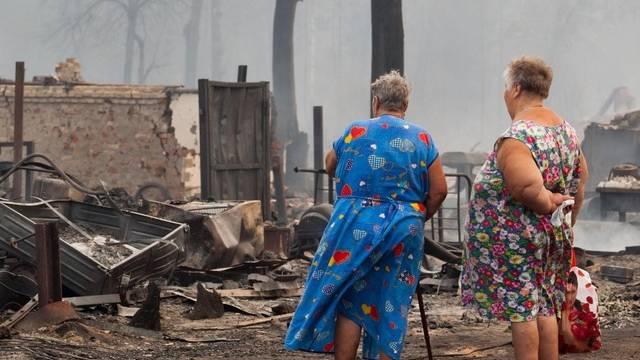 Russische Frauen betrachten ein niedergebranntes Haus