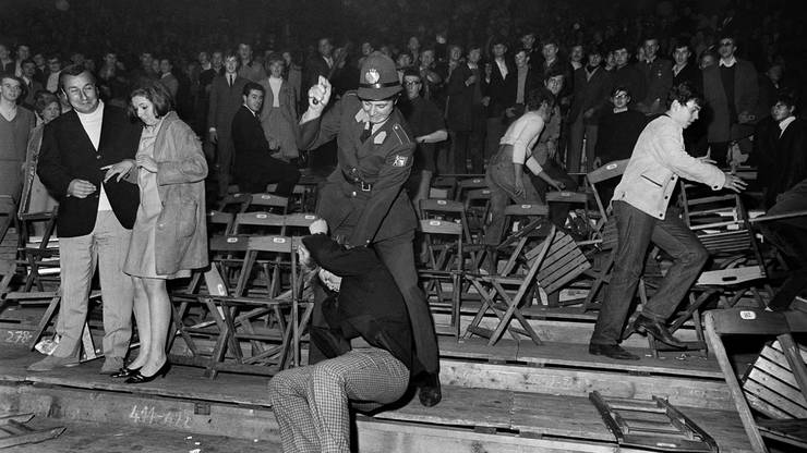 Ein Polizist knüppelt einen Konzertbesucher nieder. Am Konzert kommt es zu schweren Auseinandersetzungen.  Erst der Einsatz von rund 400 Ordnungshütern verhindert, dass die Meute die Arena komplett demoliert.
