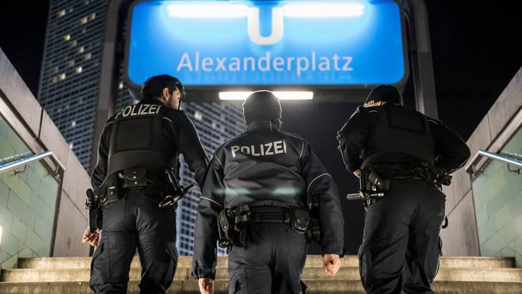 Drei Polizisten steigen die Stufen der U-Bahn-Station Alexanderplatz empor: Sie erwartet eine turbulente Nacht.