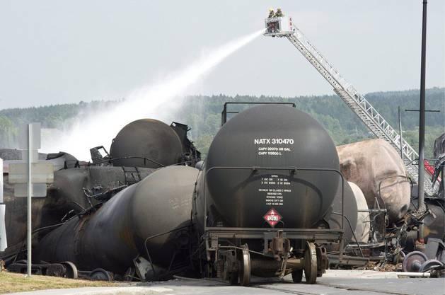 Feuerwehrleute wässern die ausgebrannten Zugwaggons