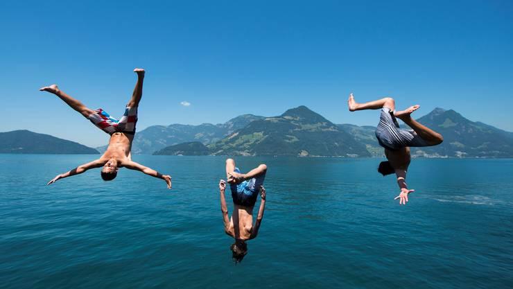 Drei junge Männer springen in den Vierwaldstättersee.