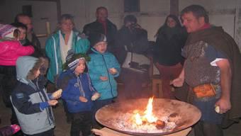 Unter Anleitung des Legionärs bringen die Wettbewerbsgewinner das Feuer mit Weihrauch zum Lodern. nn