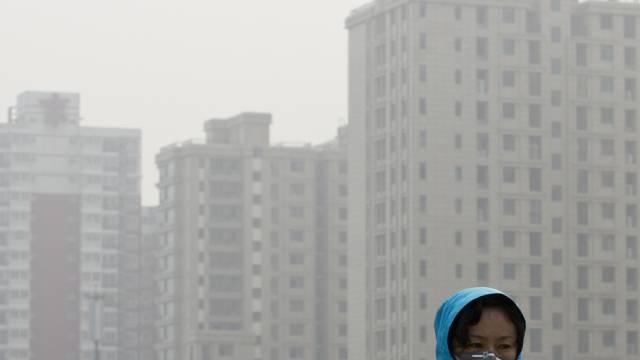 Ungesund und stickig: Frau in Peking schützt sich vor Smog