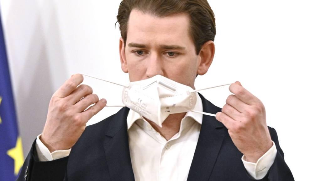 Sebastian Kurz, Bundeskanzler von Österreich, hält seinen Mund-Nasen-Schutz vor dem Gesicht. Foto: Hans Punz/APA/dpa
