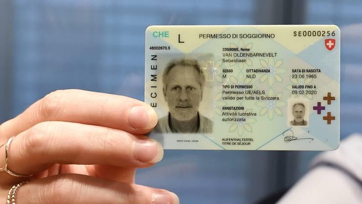 Eine Mitarbeiterin am Schalter des Migrationsamts zeigt den neuen Ausländerausweis für Bürger von EU- und Efta-Staaten