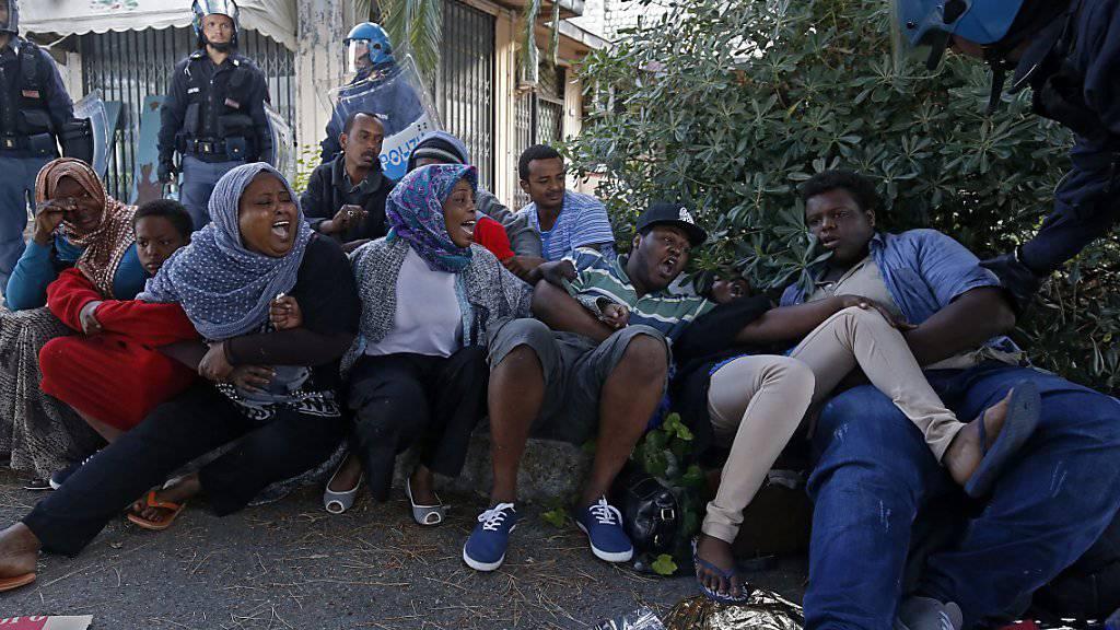 Die italienische Polizei versucht Flüchtlinge, die an der italienisch-französischen Grenze bei Ventimiglia blockiert sind, in ein Flüchtlingslager zu bringen. Die Afrikaner wollen - wie so viele andere - nach Frankreich. (Archiv)