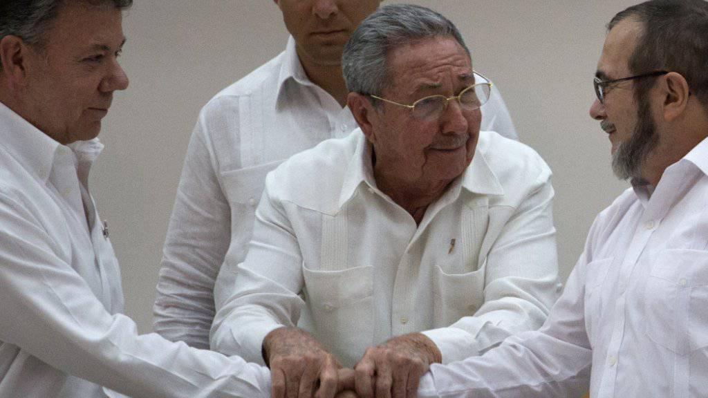Unter Vermittlung von Kubas Präsident Raul Castro (Mitte) einigten sich im September der Päsident Kolumbiens, Juan Manuel Santos (links) und der Kommandant der FARC-Rebellen, Timoleon Jimenez, auf eine juristische Aufarbeitung des Konflikts. Nun erreichten sie eine weitere Einigung. (Archiv)