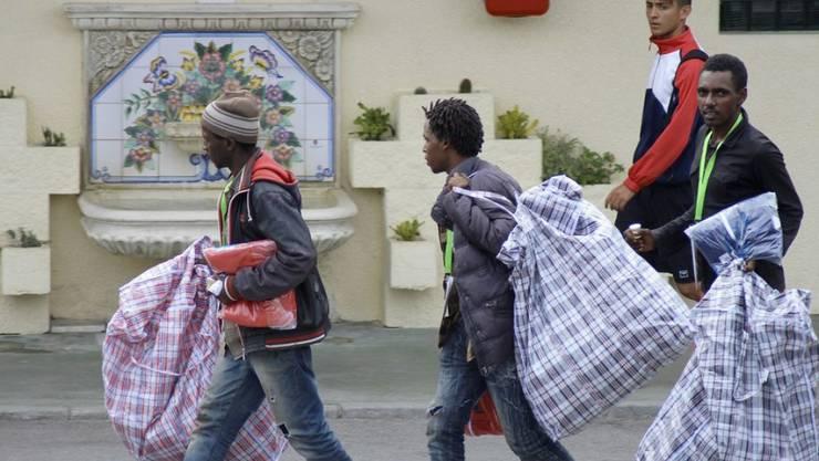 Sie haben es geschafft: Junge Flüchtlinge aus Afrika durchbrachen den Grenzzaun der spanischen Enklave Ceuta in Marokko.