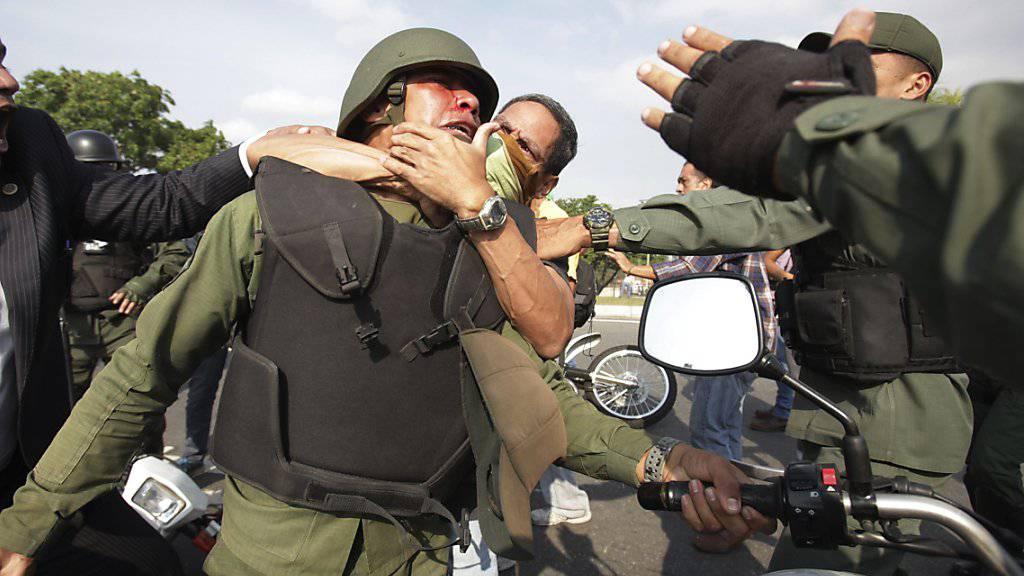 Demonstranten nehmen ausserhalb des Luftwaffenstützpunktes La Carlota bei Caracas einen Maduro-treuen Nationalgardisten in den Schwitzkasten.