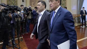 Sooronbai Dscheenbekow (r), zurückgetretener Präsident von Kirgistan, und Sadyr Schaparow, der neue Ministerpräsident von Kirgistan, treffen ein, um an einer offiziellen Zeremonie der Machtübergabe im kirgisischen Parlament teilzunehmen. Foto: Vladimir Voronin/AP/dpa