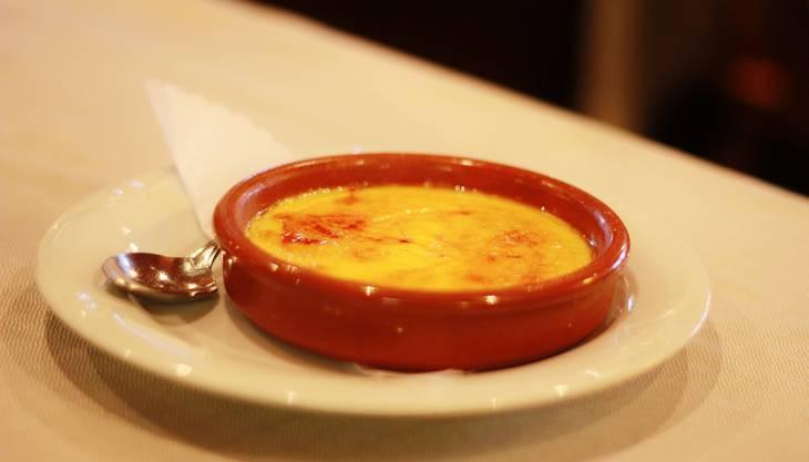 Die spanische «Crema Catalana» ist weltweit eine beliebte Nachspeise. «Nicht nur die ‹Crema Catalana› – auch die ‹Crema Caramel› wird gerne an Weihnachten als Dessert serviert», sagt der Besitzer des Restaurants «Costa Blanca» in Dietikon, Manuel Gonzalez. Allgemein seien Cremes und Puddings sowie Milchreis, ein Muss nach einer würzigen Paella oder nach Meeresfrüchten. Eine weitere weihnachtliche Süssigkeit sei auch «Turron» – eine Variante des weissen Nougats. Gonzalez fallen ganz viele spanische Nachspeisen ein, die man während der Festtage servieren könnte: Auch sehr beliebt ist «Cabello de Angel» (Engelshaar). Dabei handelt es sich um eine Süssspeise, die aus den karamellisierten Fasern einiger spezieller Kürbisarten hergestellt wird. Der Restaurantbesitzer freut sich privat besonders auf die «Turron» sowie auf sogenannte «Polvorones». Letzteres ist ein Schmalzgebäck, dass nicht nur in Spanien sondern auch in Lateinamerika sowie den Phillipinen beliebt ist. Rezept aus dem «Costa Blanca» Um die «Crema Catalana» zuzubereiten, geben Sie das Eigelb, Zucker und die Maizena in eine Schüssel. Danach gut verrühren. In der Zwischenzeit die Milch aufkochen lassen und die Kerne aus der Vanilleschote in die Milch geben. Anschliessend den Inhalt der Schüssel in die kochende Milch umleeren und konstant rühren – dabei aufpassen, dass keine Klumpen entstehen. Wenn das Ganze cremig wird, den Topf von der Herdplatte nehmen und den Inhalt in kleine Tonschalen giessen. Danach die Creme kaltstellen. Vor dem Servieren mit einer feinen Zuckerschicht bedecken und diese mit einem Bunsenbrenner erhitzen, damit eine Karamellkruste entsteht. 1 L Milch1 Vanilleschote180 g Eigelb150 g Zucker70 g Maizena