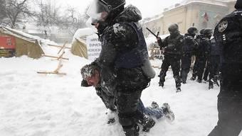Polizisten in Kiew nehmen einen Demonstranten fest und räumen ein Zeltlager vor dem Parlament.