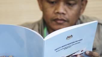 Ein Angehöriger eines Passagiers von Flug MH370 liest den Abschlussbericht zum verschwinden des Flugzeugs der Malaysia Airlines.