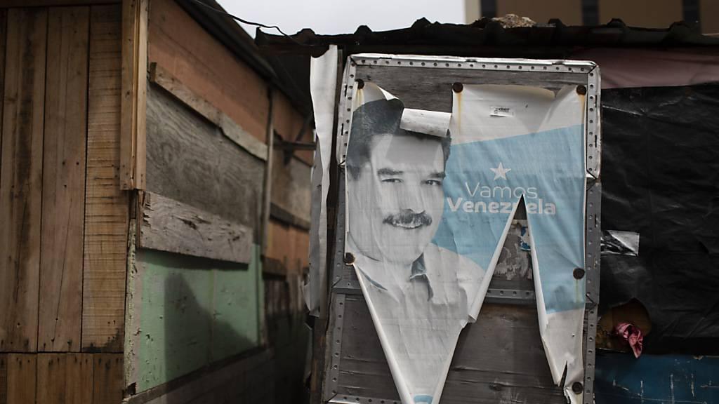 Ein altes Wahlkampfplakat mit dem venezolanischen Präsidenten Maduro bedeckt die Tür einer Baracke in Caracas. Fünf Monate vor den geplanten Parlamentswahlen hat der Oberste Gerichtshof Venezuelas den Vorstand einer der wichtigsten Oppositionsparteien des Landes ausgetauscht. Foto: Ariana Cubillos/AP/dpa