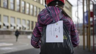 Schulmädchen mit Hausaufgaben-Paket: Die Erziehungsdirektoren wollen das laufende Schuljahr trotz Fernunterricht als vollwertig gelten lassen. (Themenbild)