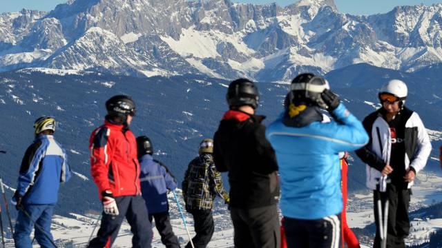 Skifahrer stehen auf einer Piste vor dem Dachsteinmassiv (Archiv)