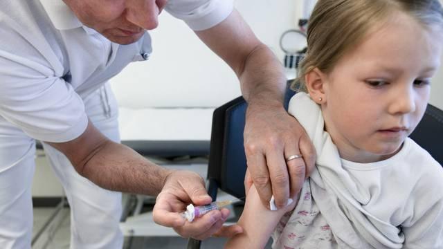 Ein Hausarzt setzt einer jungen Patientin eine Spritze (Archiv)